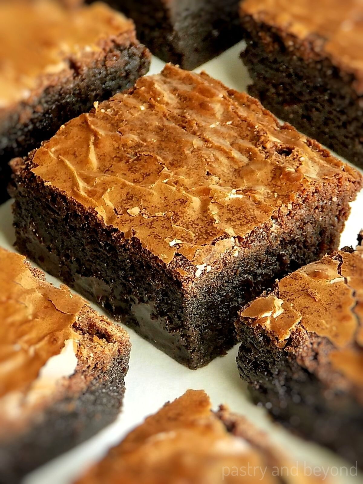 Brownies without Cocoa Powder with a crackly top on a white surface.