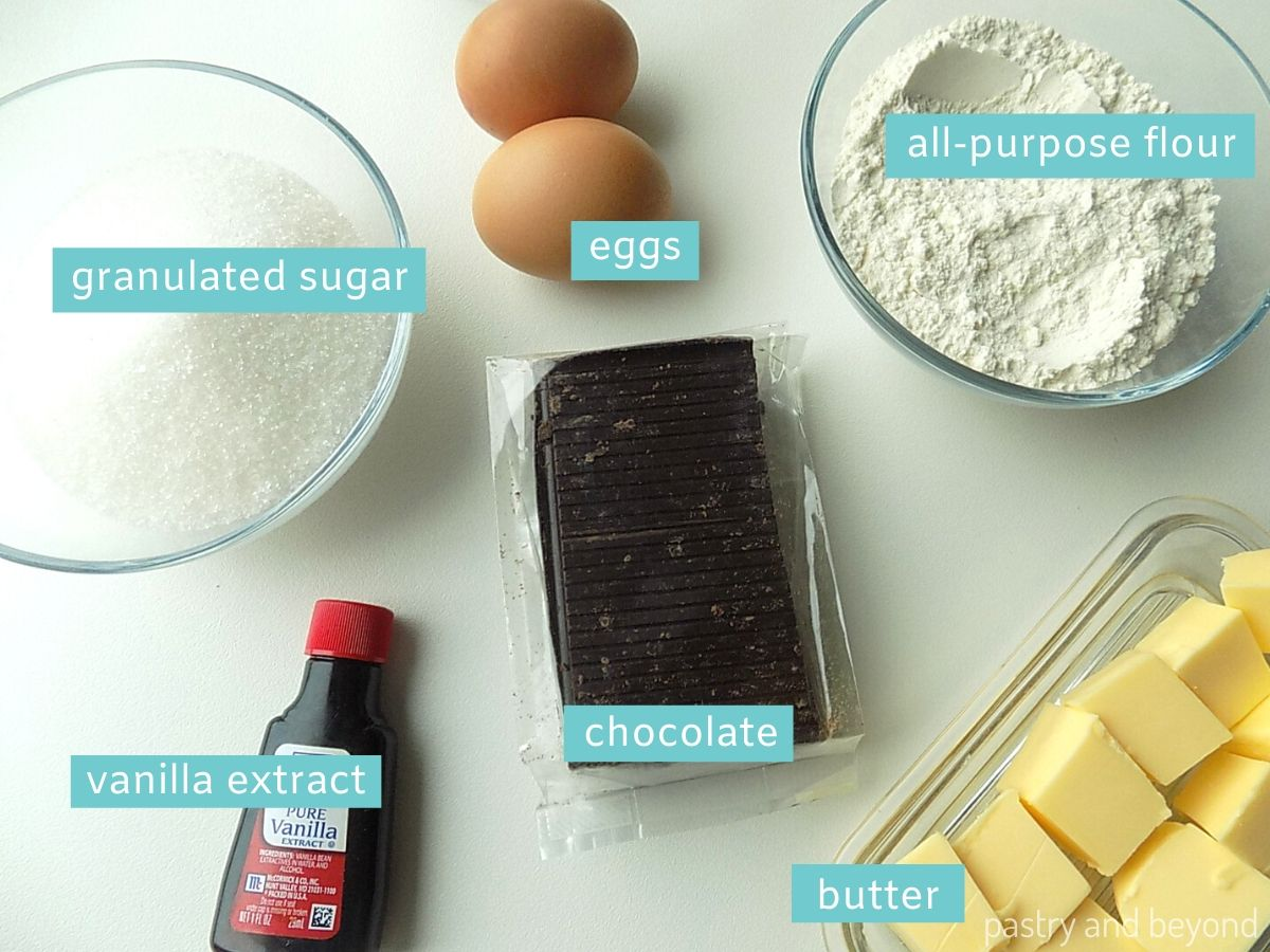 Each ingredient of a brownie: granulated sugar and all purpose flour in small bowls, vanilla extract bottle, chocolate, eggs and butter on a white surface.