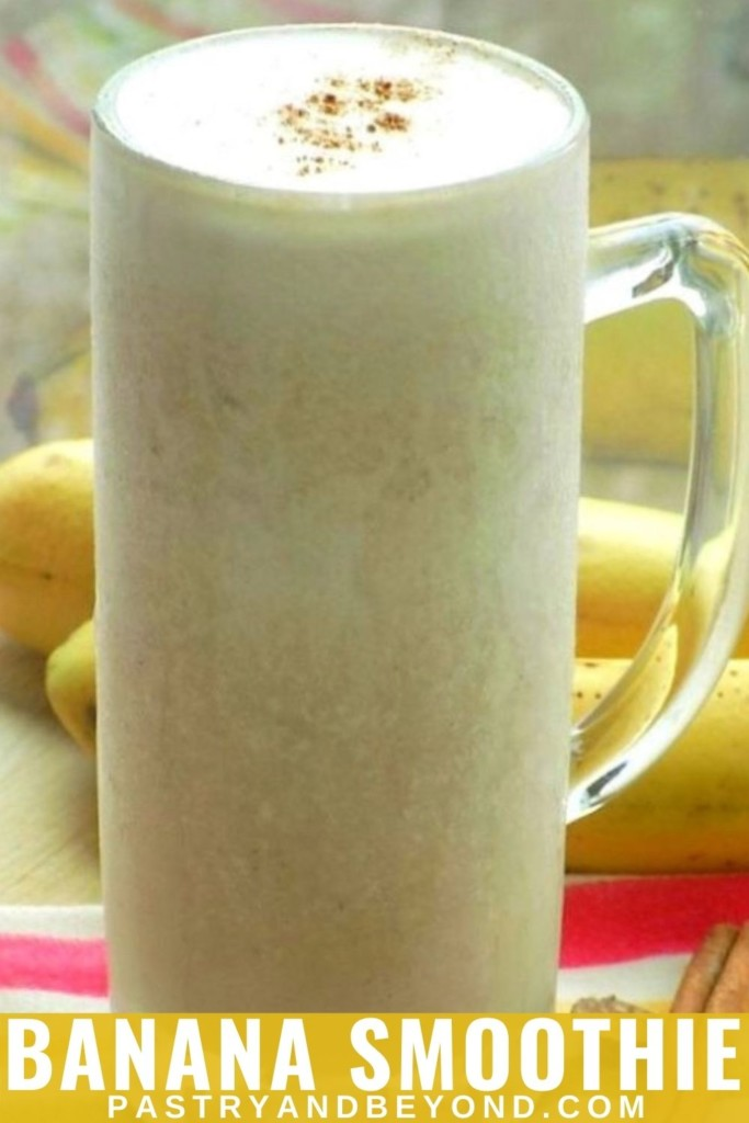 A large glass of banana smoothie with bananas in the background.
