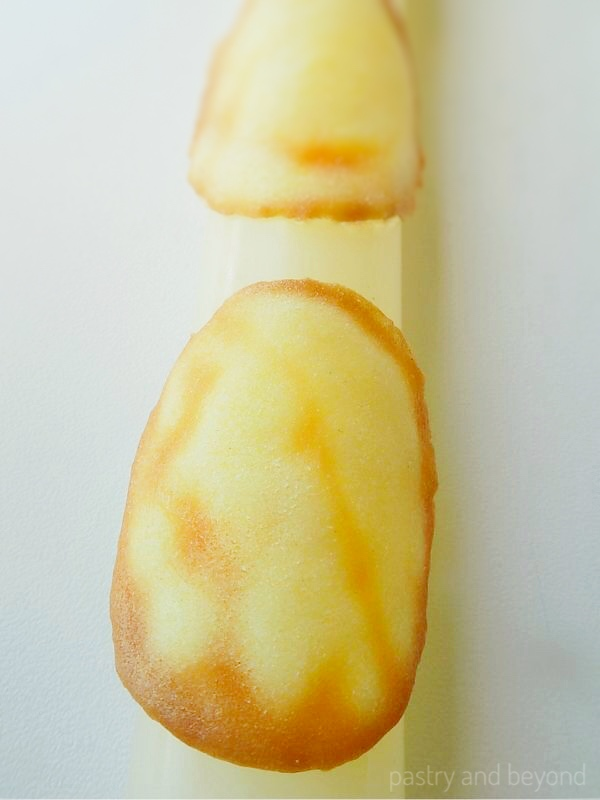Tuile cookies on a rolling pin to make the curved shape.