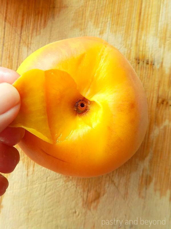 Peeling a peach from the bottom side with fingers after blanching step.