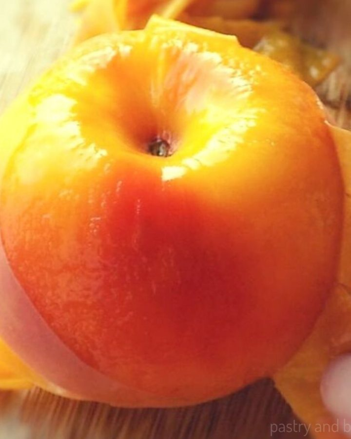 Peeling a peach with fingers on a wooden surface.