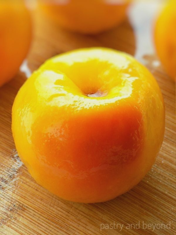Overhead view of peeled peach on a wooden background.