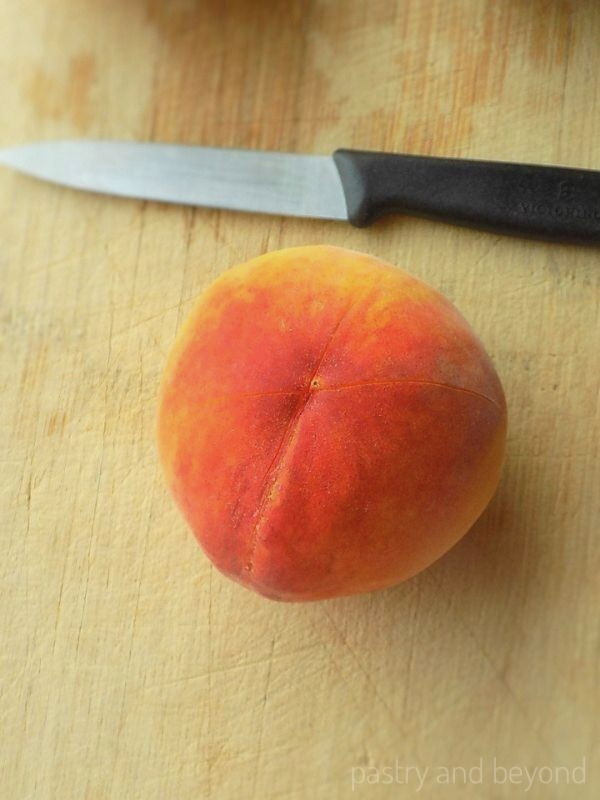 Peach with X sign at the bottom on a wooden surface with a knife.