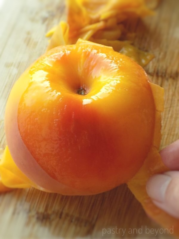 Peeling a peach with fingers on a wooden surface after blanching.
