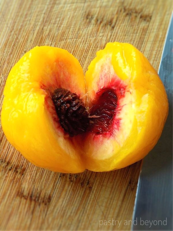 Peach cut in half, pit in the middle.