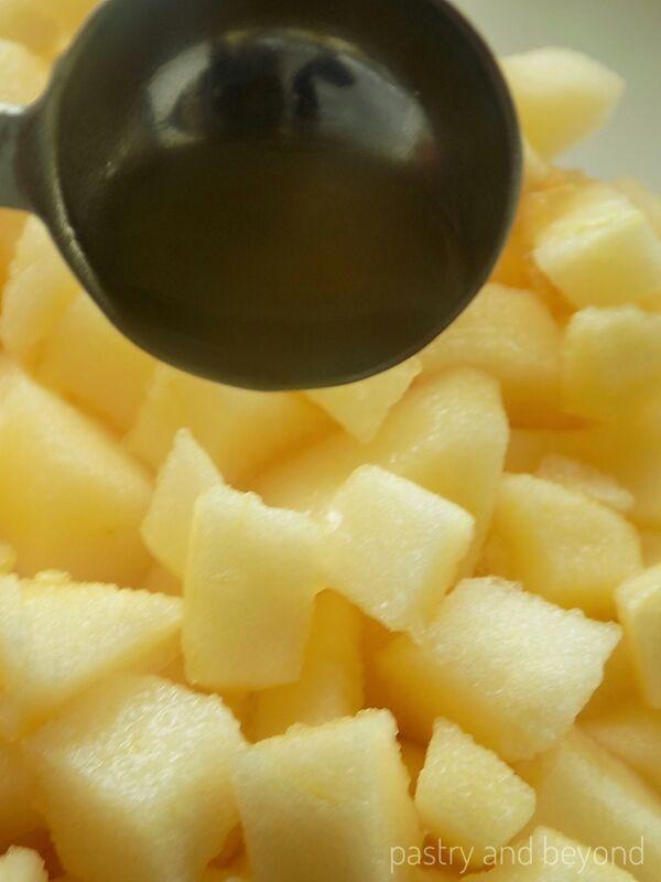 Adding lemon juice over the chopped apples.