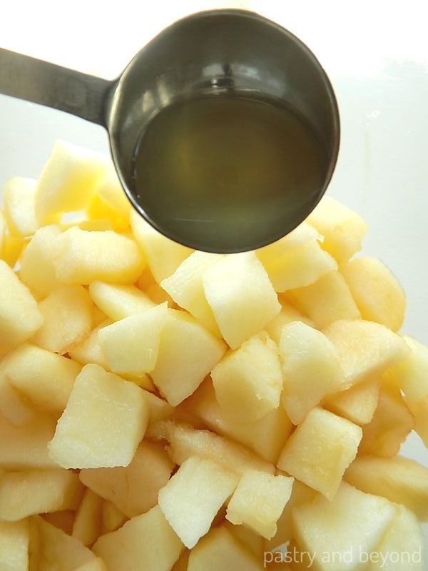 Adding lemon juice over the chopped apples for apple turnover filling.