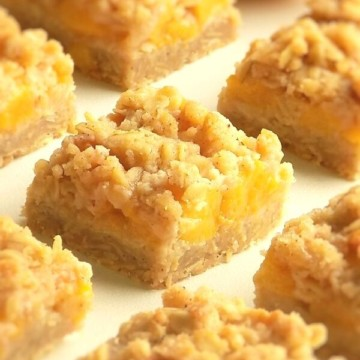 Peach crumb bars in a row on a white surface.
