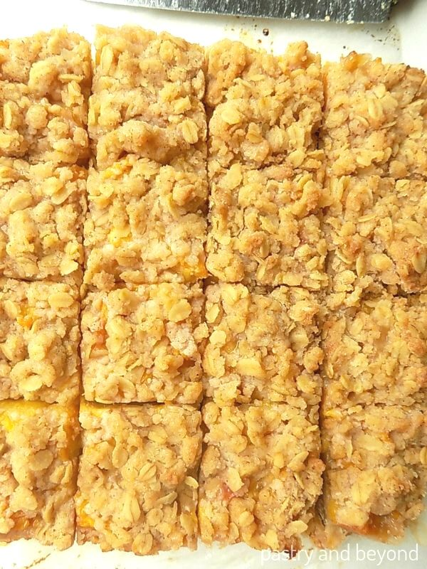 Overhead view of peach crumb bars that are cut into 16 pieces.