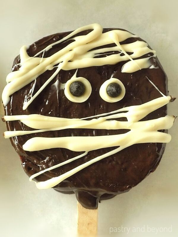 Chocolate dipped apple slice with a mummy design on a baking sheet.