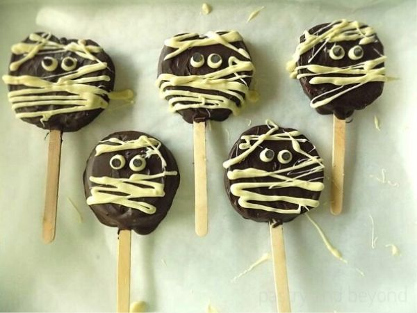 Chocolate covered apple slices on a parchment paper.