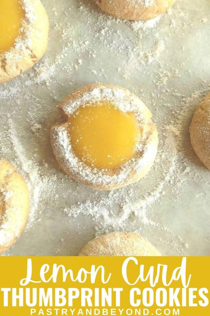 Lemon curd cookies on parchment paper with powdered sugar on top.