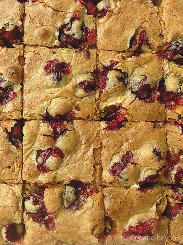 Cranberry blondie with crinkly top cut into pieces.
