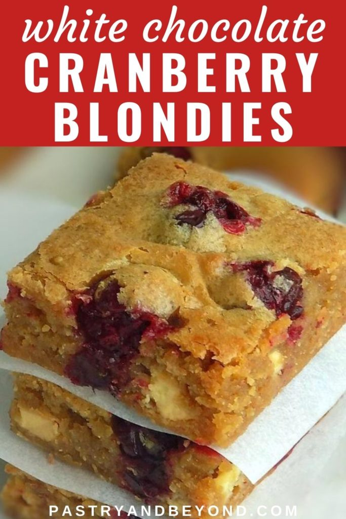 Stacked cranberry white chocolate blondies with text overlay
