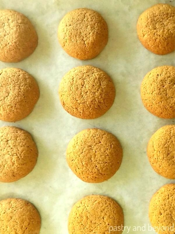 Pumpkin spice cookies on a parchment paper lined baking sheet.