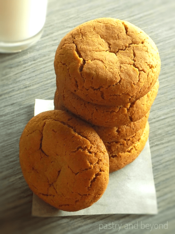 Stacked ginger molasses cookies, glass of milk in the background.