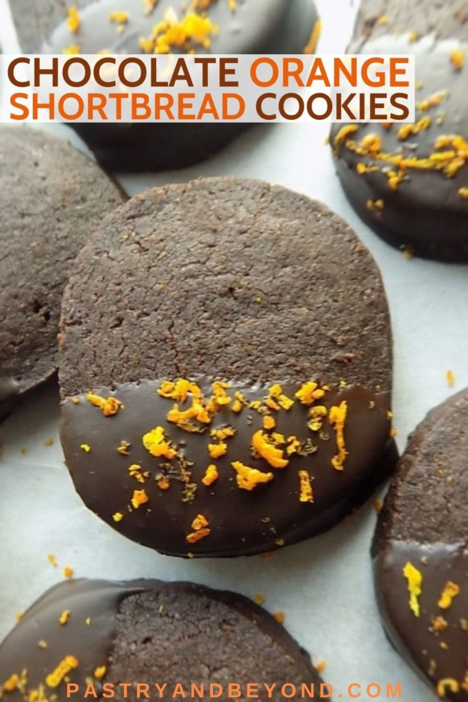 Chocolate dipped cocoa orange shortbread cookies on a white surface.