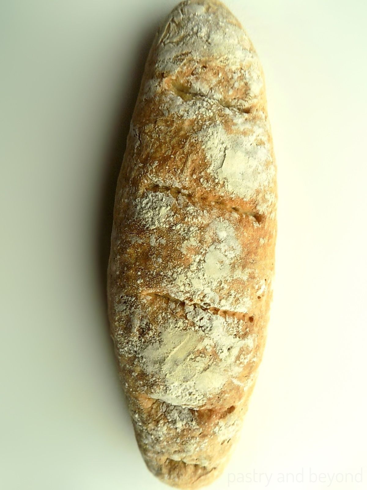 Homemade artisan long loaf bread on a white surface.