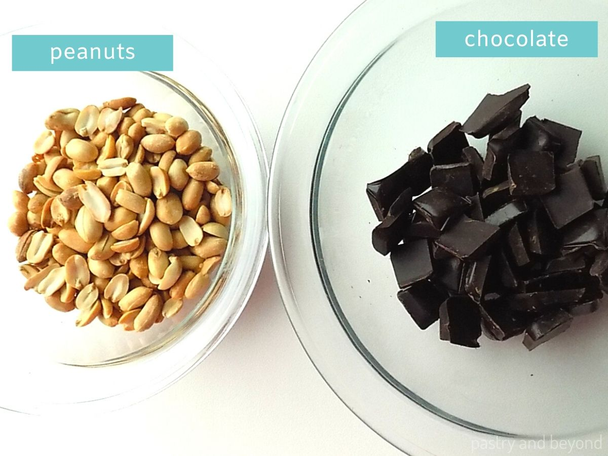 Ingredients for Peanut Clusters: peanuts in a bowl and chopped chocolate in another bowl on a white surface.