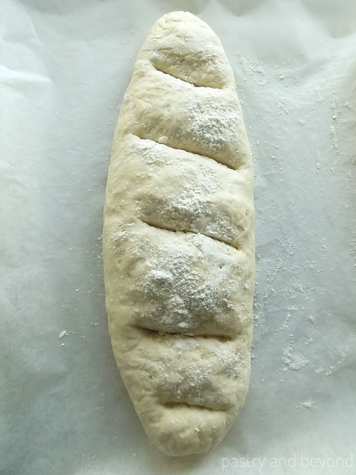 Long loaf with slashes on parchment paper.
