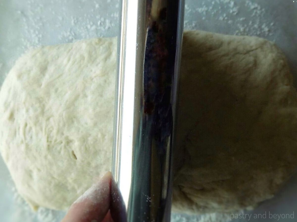 Cutting the rectangle dough in half with a pastry scraper.