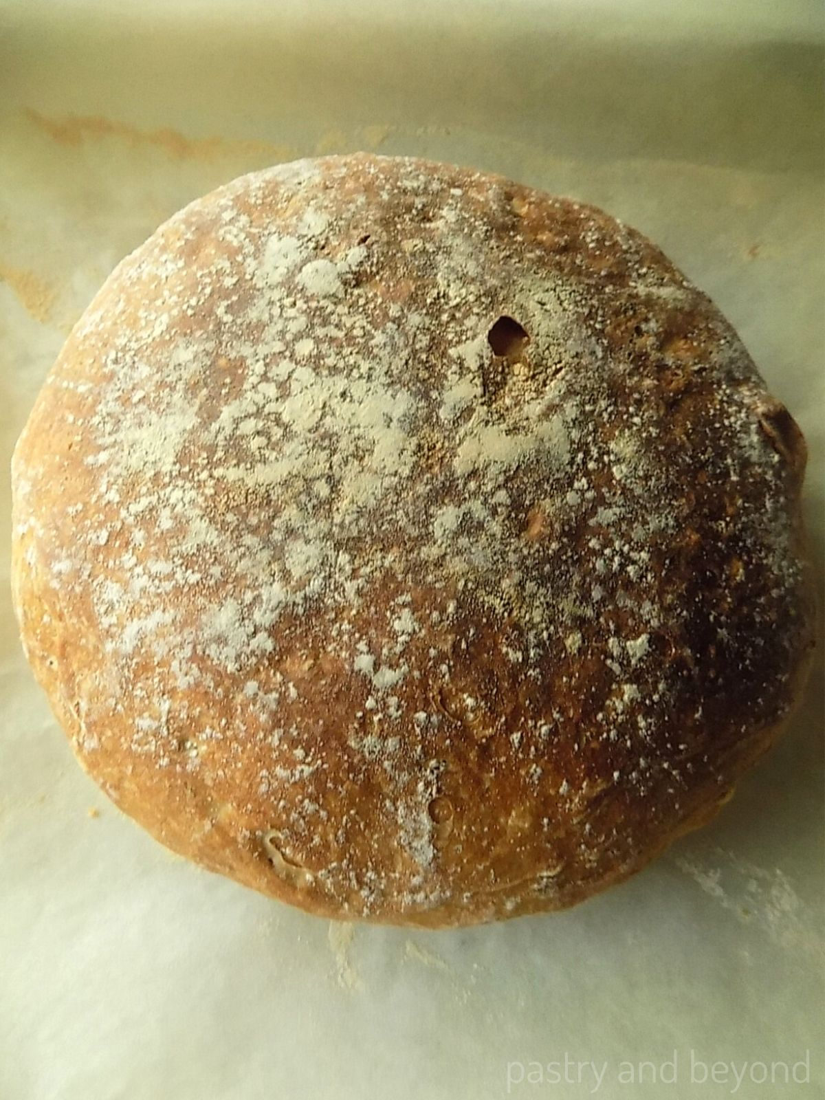 Round no knead bread that is baked without dutch oven on parchment paper.