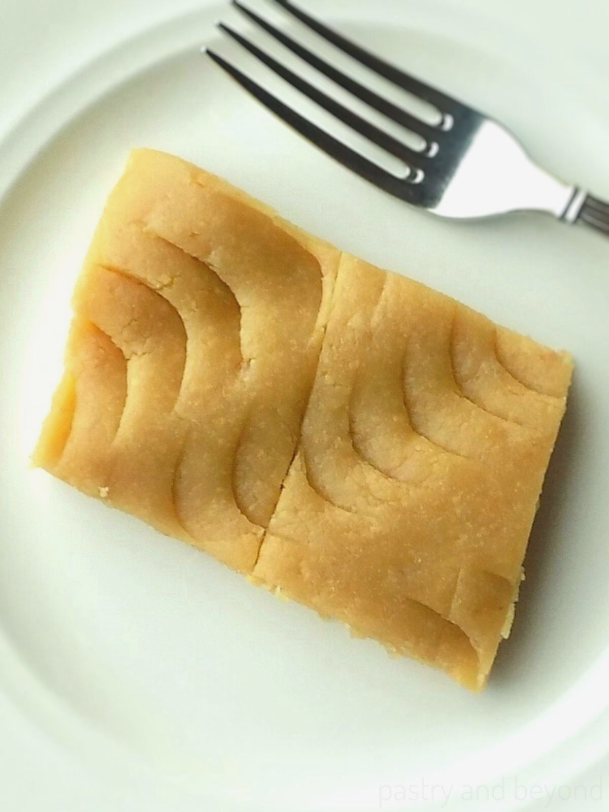 Turkish Halva on a white plate with a fork.