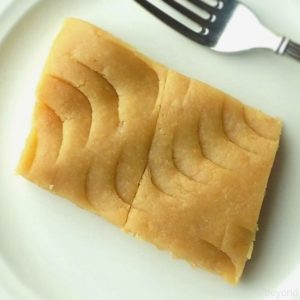 Slice of Turkish flour halva on a plate with a fork.