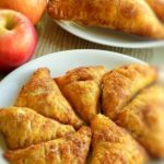 Small apple turnovers on a white plate, large apple turnovers and apples in the background.