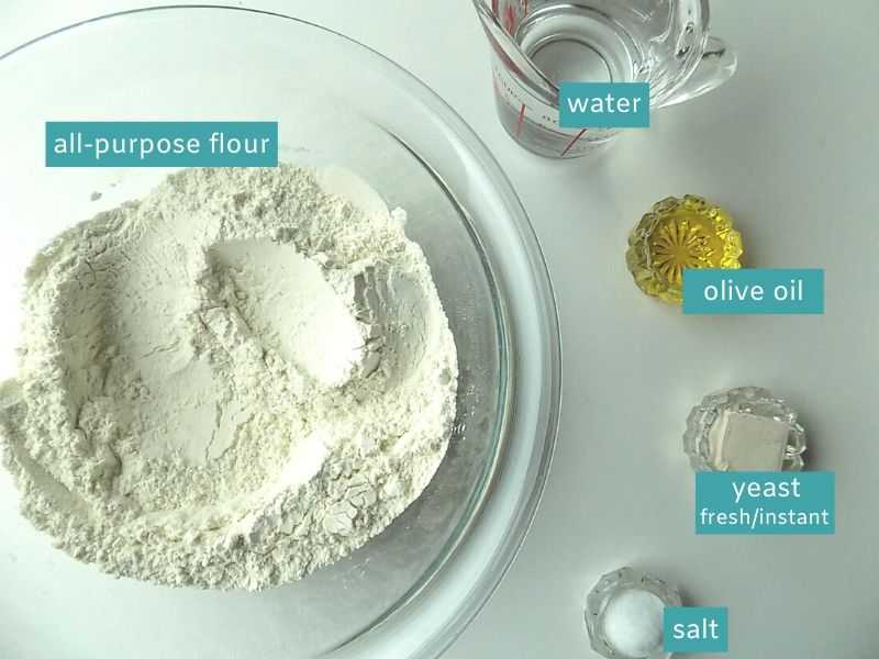Ingredients for pizza dough on a white surface; flour, water, olive oil, fresh yeast and salt