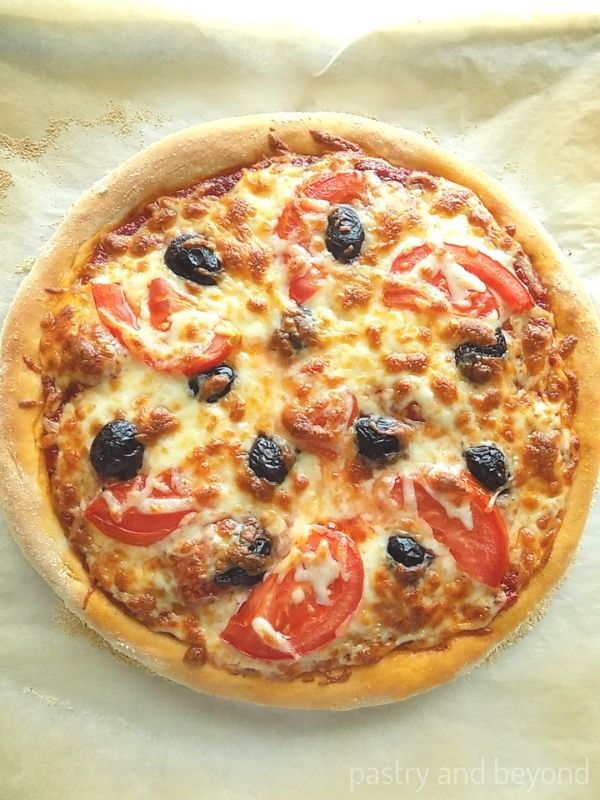 Baked pizza with cheese, tomato and black olives.