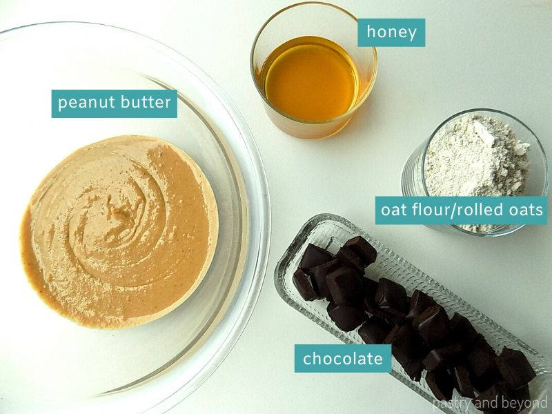 Ingredients for chocolate peanut butter no bake bars on a white surface in glass dishes.