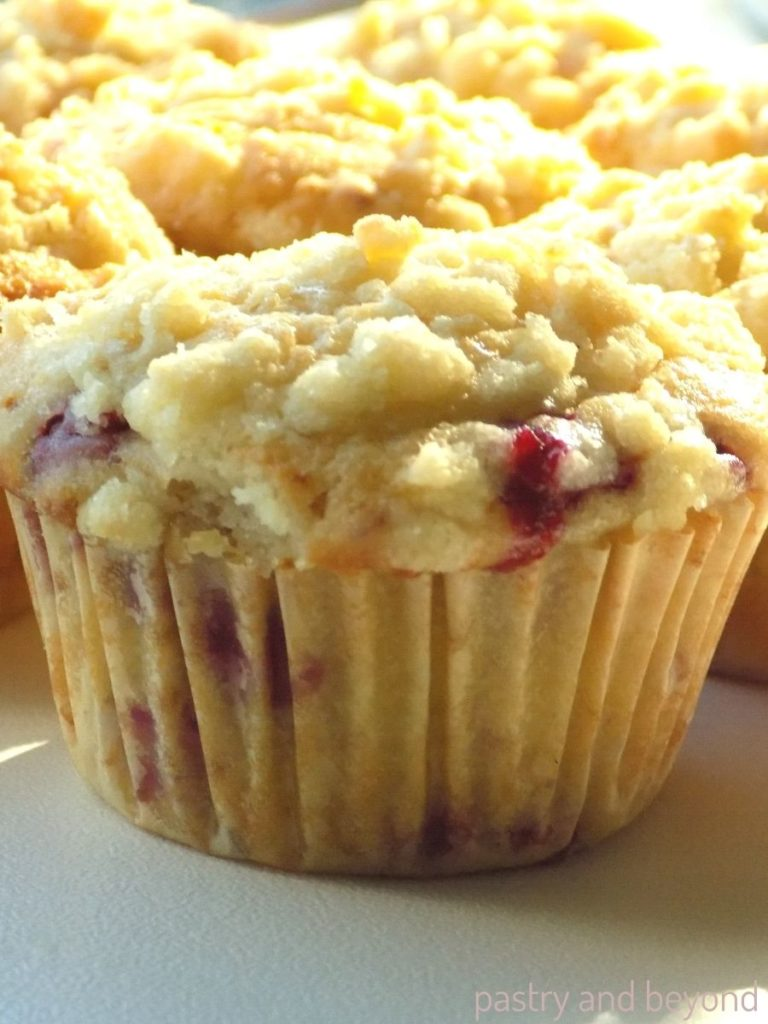 Raspberry streusel muffins on a white surface.