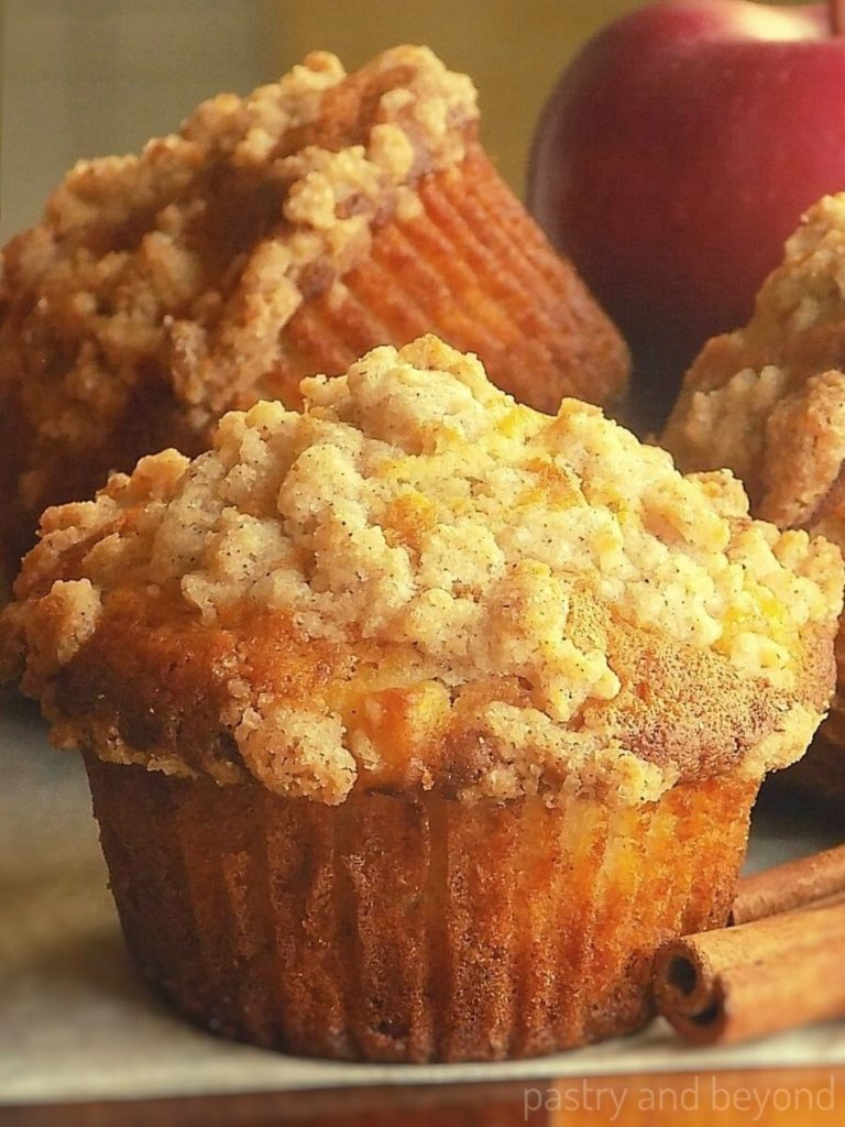 Apple muffins with crumble topping,   and apple on the background and cinnamon sticks infront of the muffins.