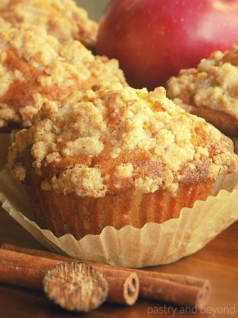 Apple crumble muffin removed from the paper liner behind the nutmeg and cinnamon stick.