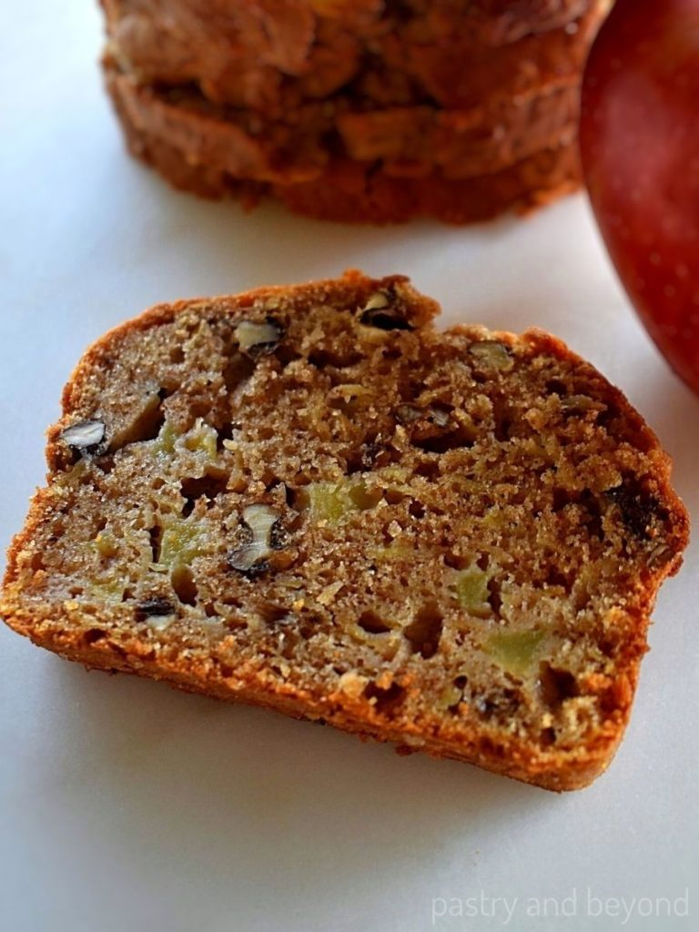 Slice of apple loaf on a white surface, apple on the right side and stacked slices on the back.