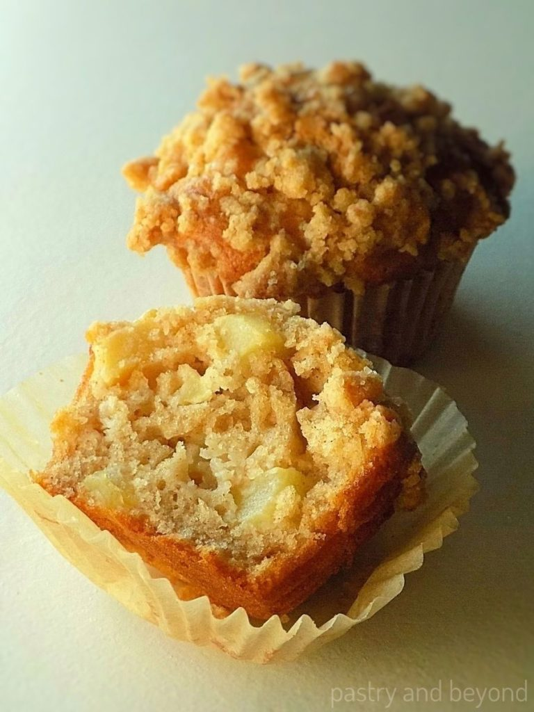 Showing the half of the apple muffin that is placed in front of whole apple muffin with streusel topping.