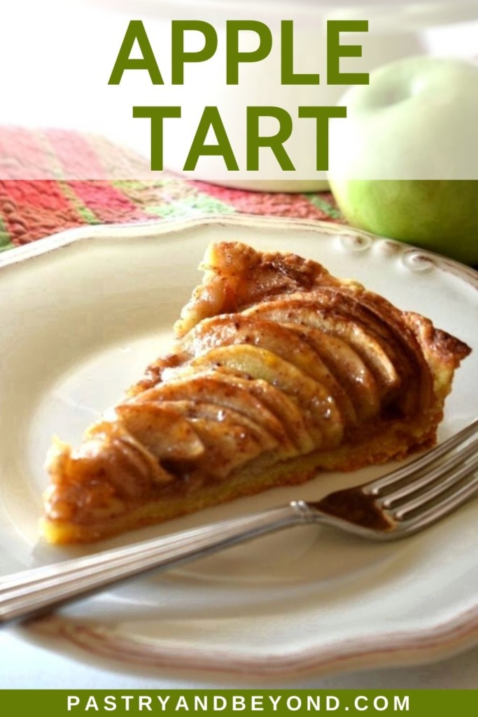 A slice of apple tart on a plate with green apple in the background.