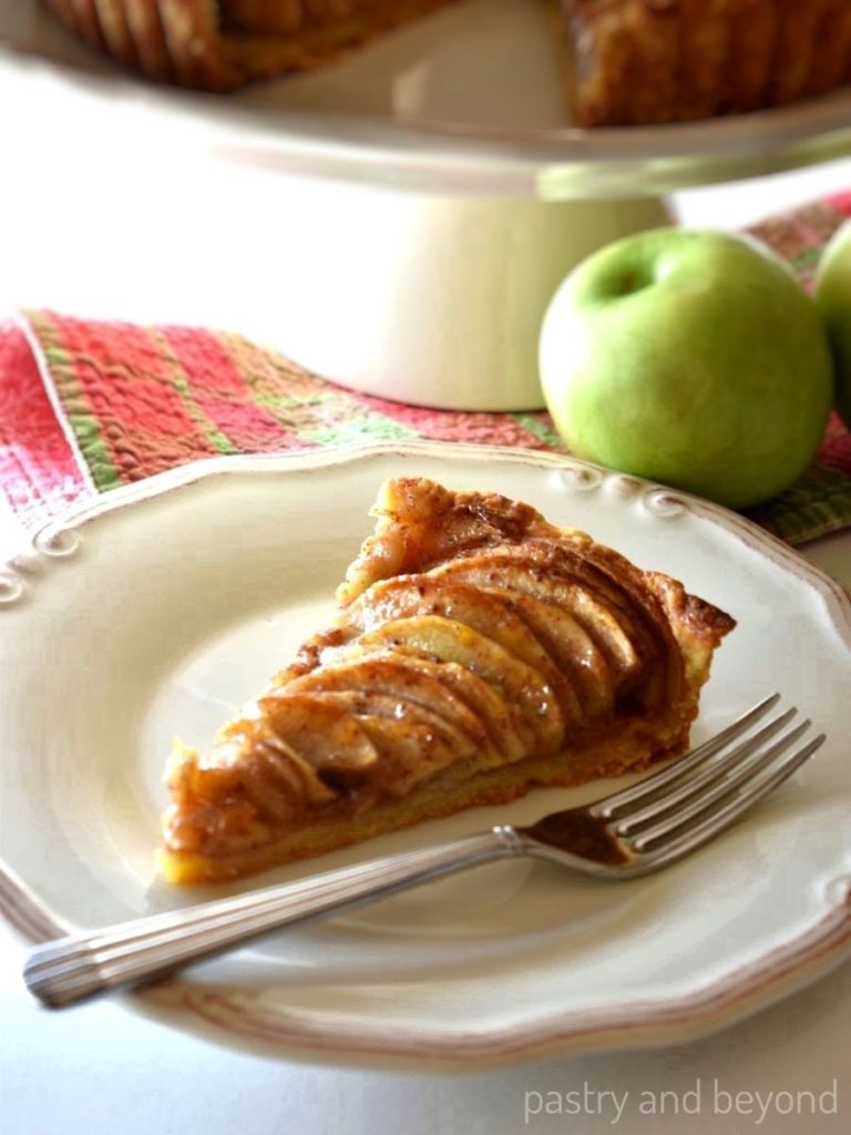 Apple tart in a plate with a fork and the serving plate is on the background.