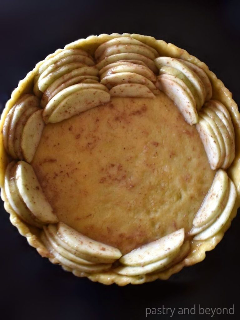 Placing the apples into the unbaked tart crust.