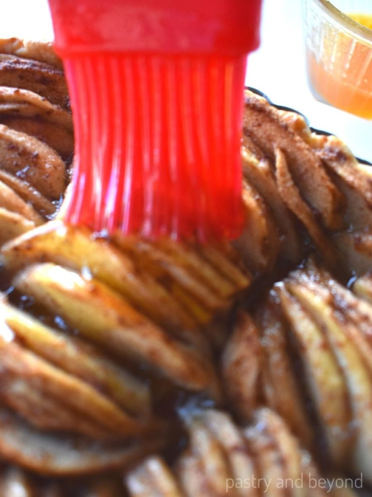 Brushing the top of the apples with apricot glaze.