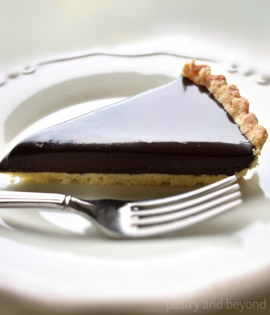 Side view of chocolate ganache tart in a plate with a fork.