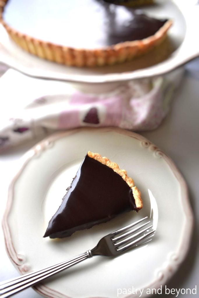 A slice of chocolate ganache tart in a plate with a fork, the serving plate with tart in the background.