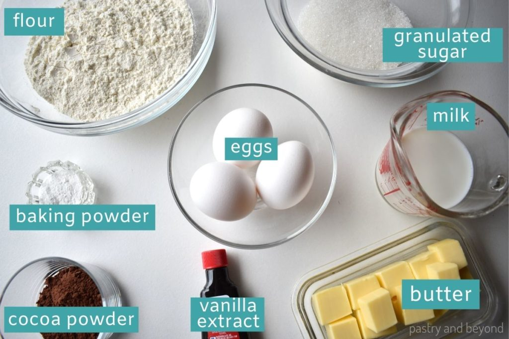 Ingredients for marble cake loaf on a white surface.