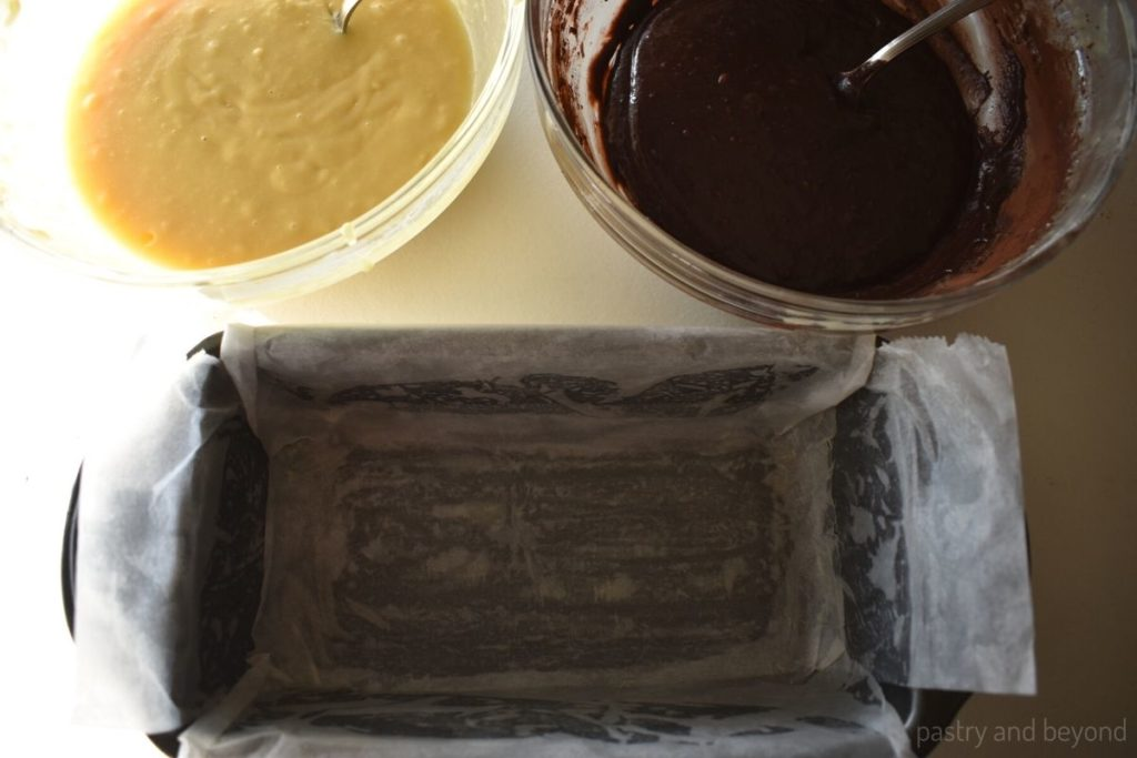 Cocoa batter and vanilla batter with spoons and loaf pan covered with parchment paper.