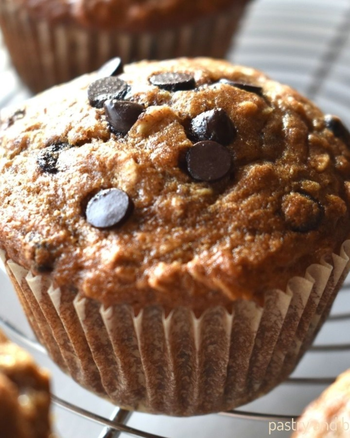 Banana oatmeal chocolate chip muffins on a wire rack.