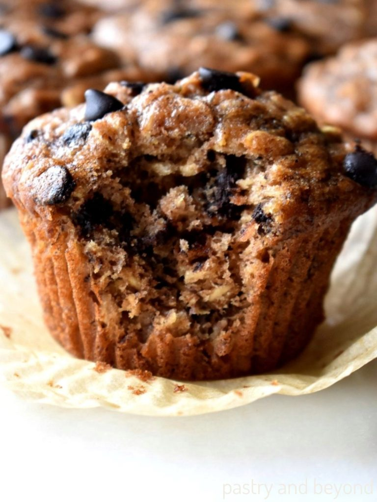 Banana oatmeal chocolate chip muffin with a bite taken from it.