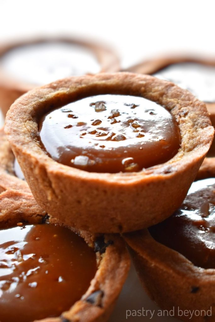 Stacked caramel cookie cups with sea salt on top.