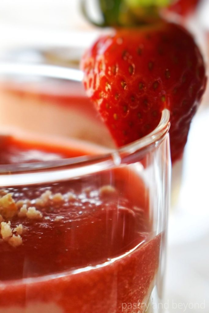Strawberry that is cut from the middle attached to the side of the serving glass.